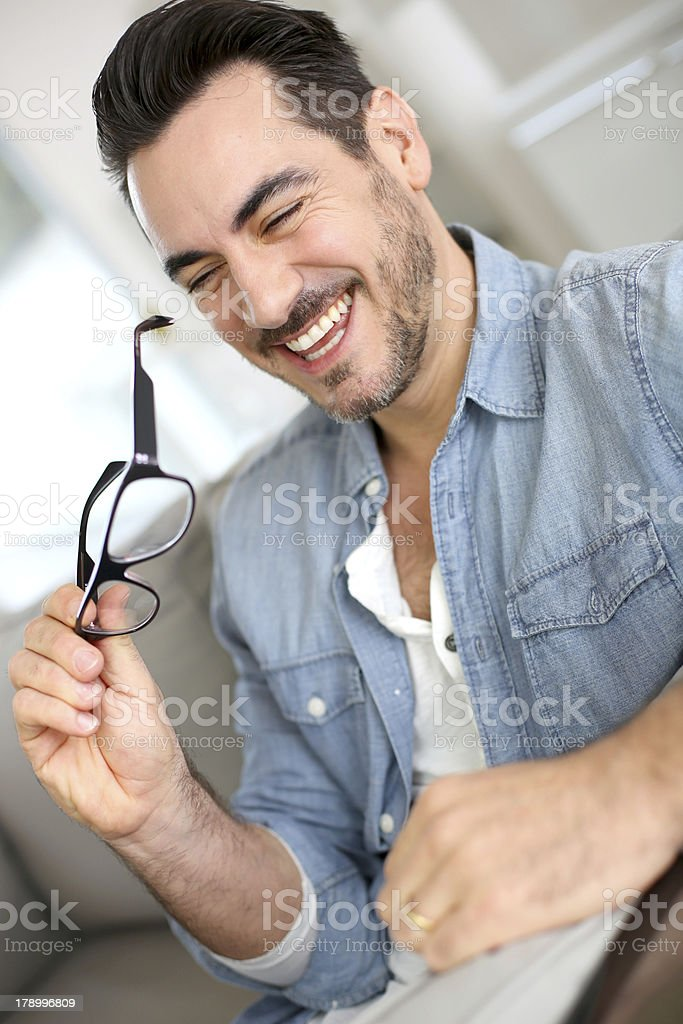 Smiling man with eyeglasses in hand royalty-free stock photo