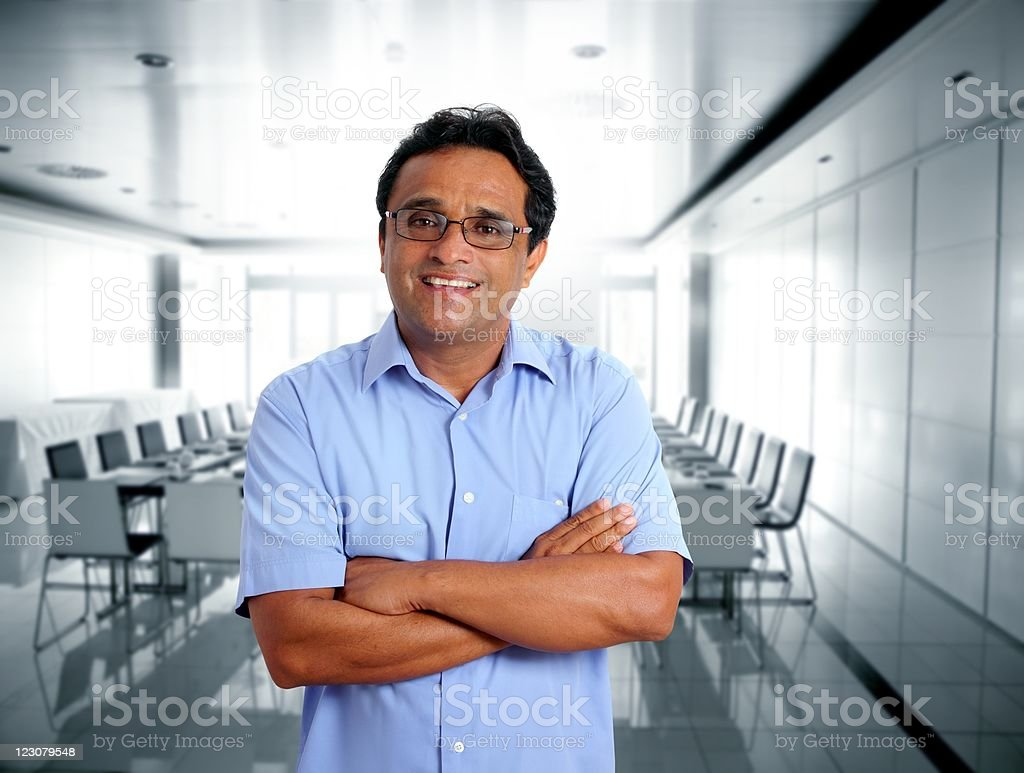 Smiling man with folded arms in a room with table and chairs stock photo