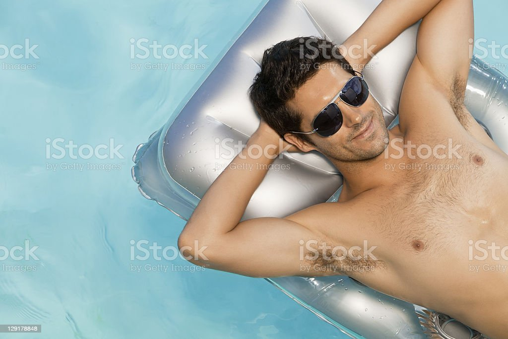 Smiling man with hands behind hand on raft stock photo