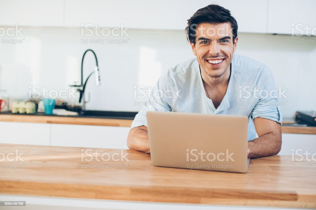 Smiling man with laptop in the kitchen stock photo