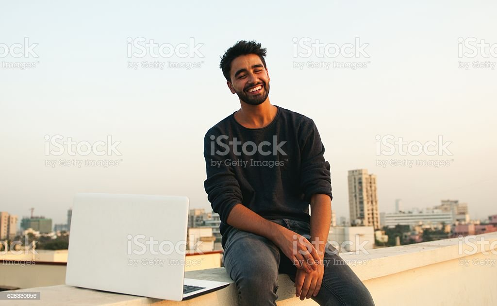 Smiling man with laptop on rooftop. stock photo