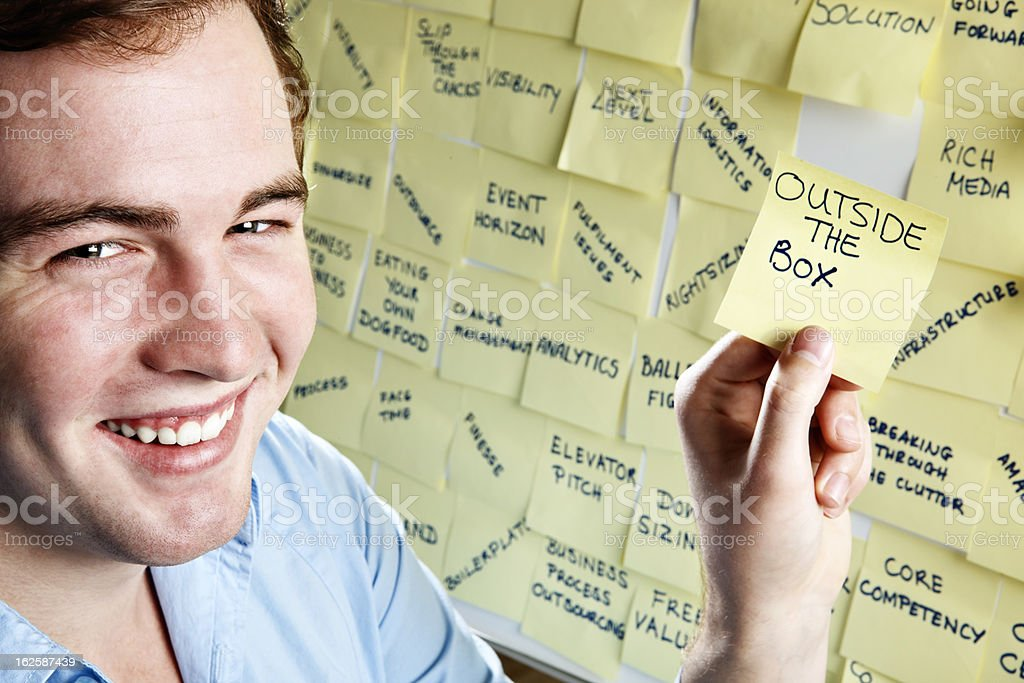 Smiling man with note 'Outside the Box' by buzzword noticeboard royalty-free stock photo