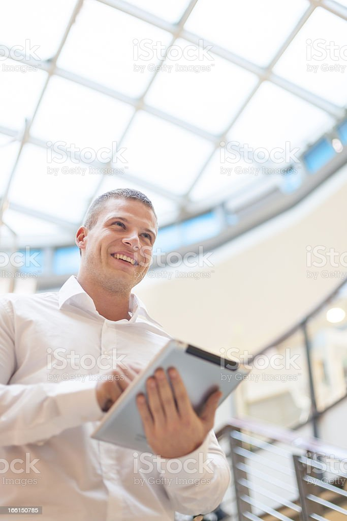 Smiling Man with tablet computer in modern busine stock photo