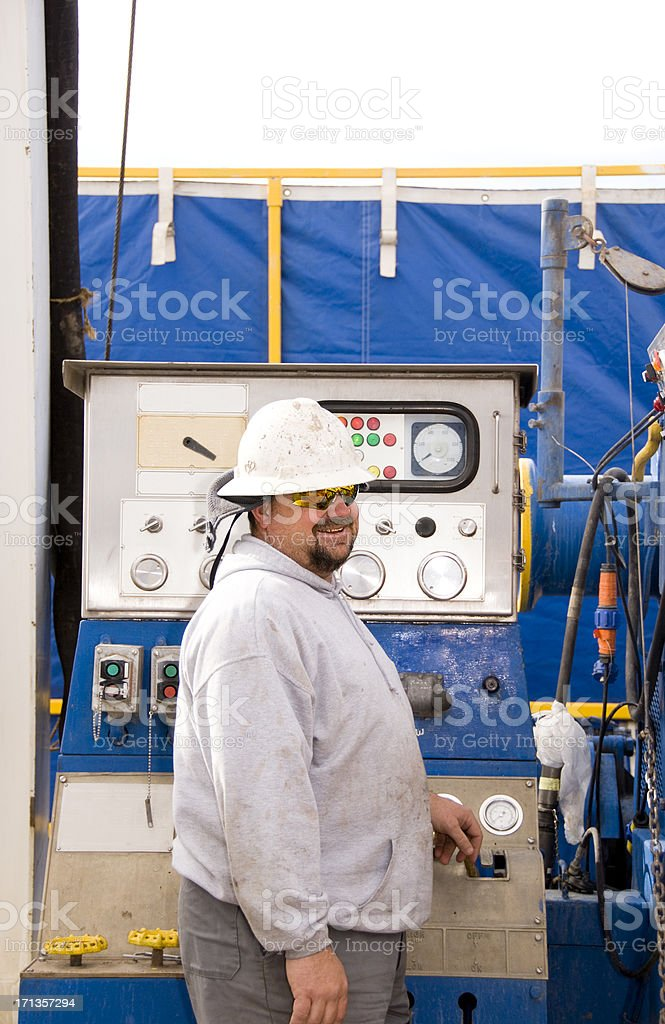 Smiling man working in an oil field royalty-free stock photo