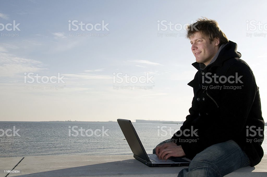 Smiling man works on laptop outside royalty-free stock photo