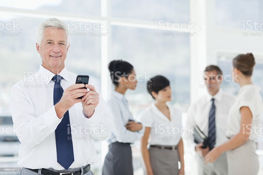 Smiling manager holding his cellphone with the team behind him stock photo