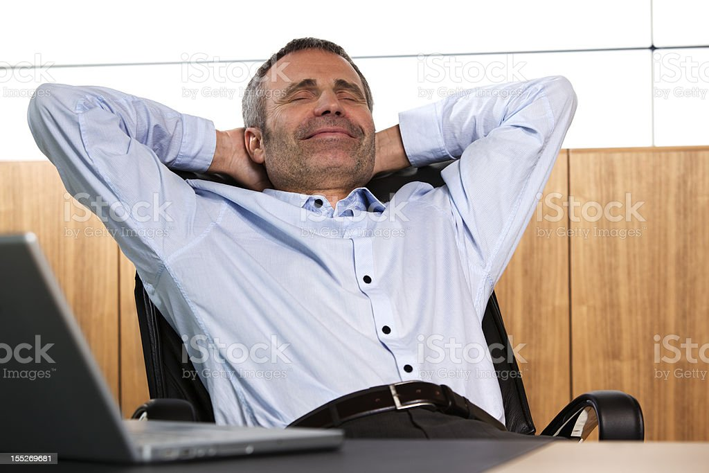 Smiling manager relaxing in office chair. stock photo