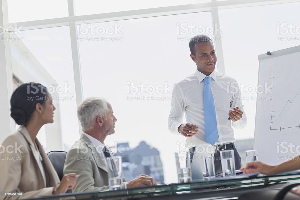 Smiling manager standing in front of colleagues royalty-free stock photo