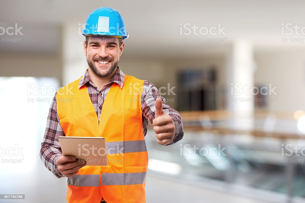 Smiling manual worker in blue helmet gesture thumb up stock photo