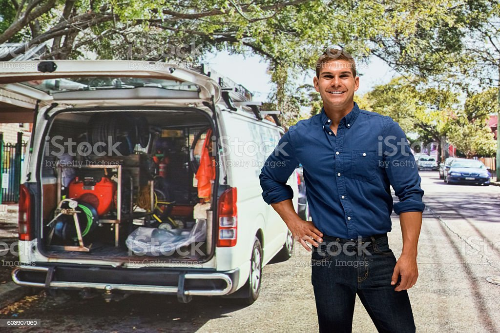 Smiling manual worker in front of van outdoors stock photo