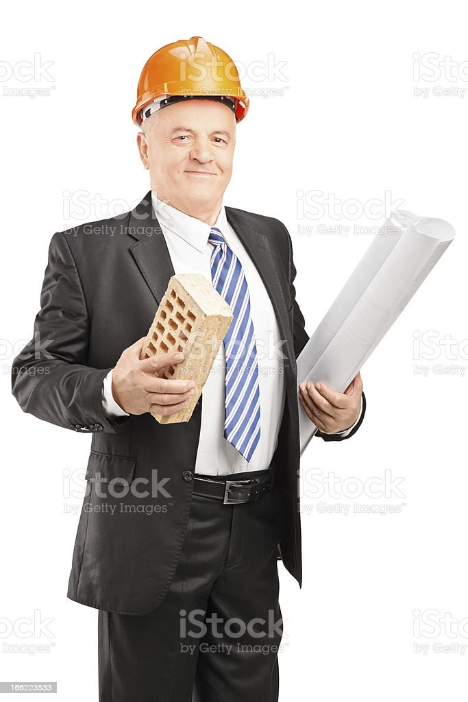 Smiling mature architect holding a brick and blueprint royalty-free stock photo