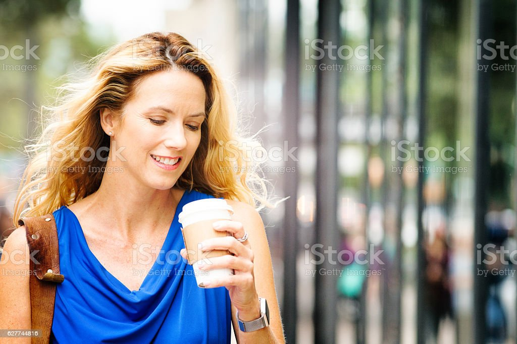 Smiling mature blonde happy American woman anticipating drinking coffee stock photo
