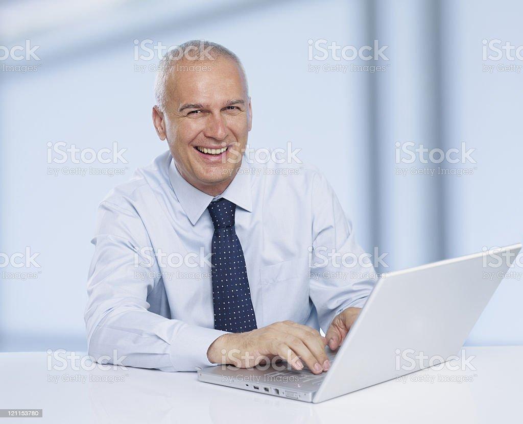 smiling mature businessman using laptop stock photo