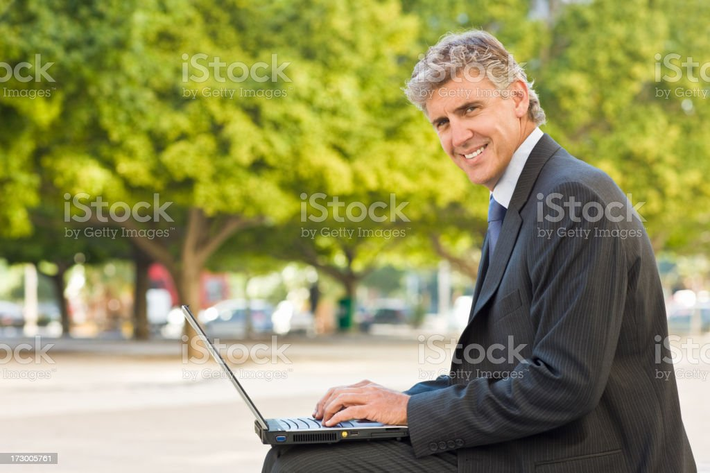 Smiling mature businessman using laptop royalty-free stock photo