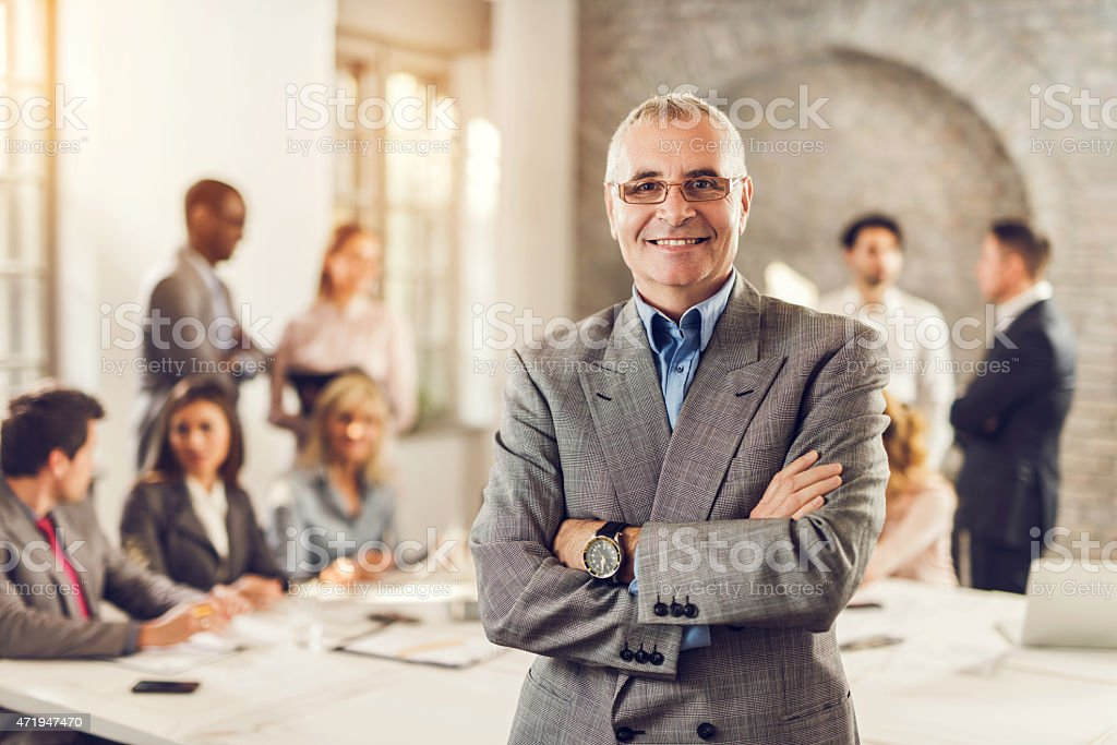 Smiling mature businessman with crossed arms in the office. stock photo