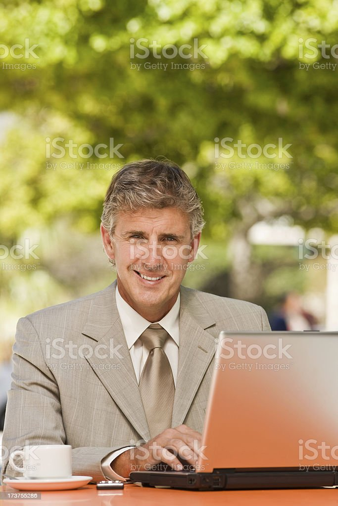 Smiling mature businessman working on laptop royalty-free stock photo