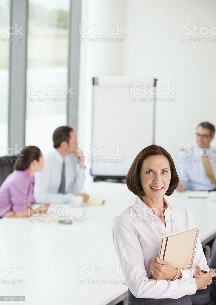Smiling mature businesswoman with business executives in meeting at board room royalty-free stock photo