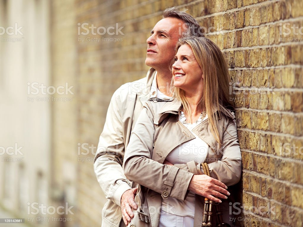 Smiling mature couple embracing and standing next to brick wall. royalty-free stock photo