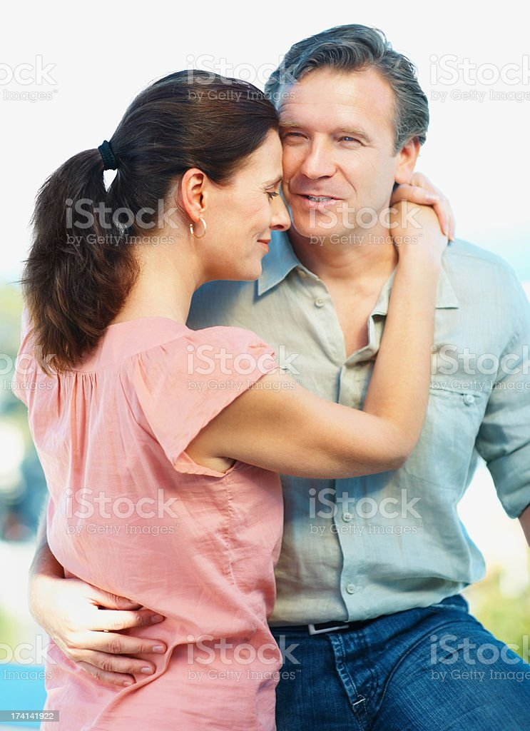 Smiling mature couple embracing eachother outside stock photo