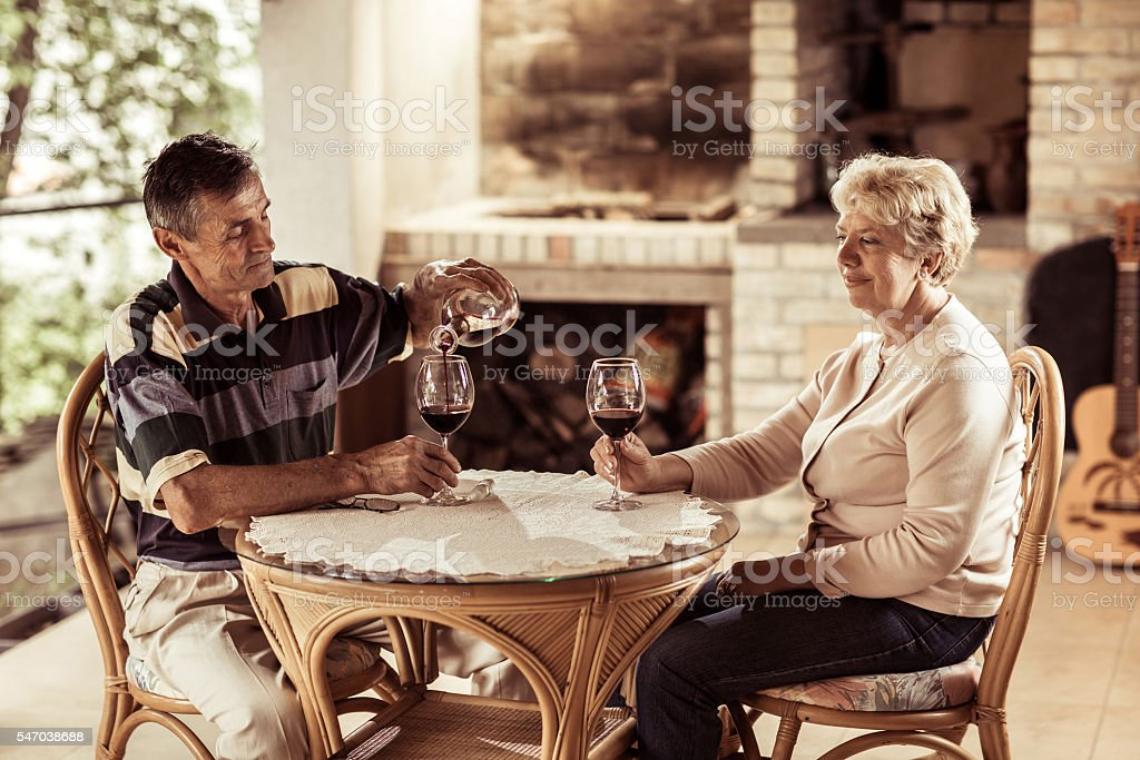 Smiling mature couple enjoying with red wine on their terrace. stock photo