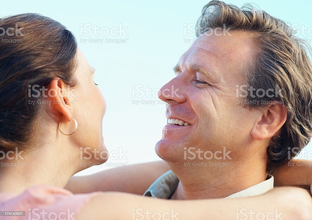 Smiling mature couple looking at each other with arms around stock photo