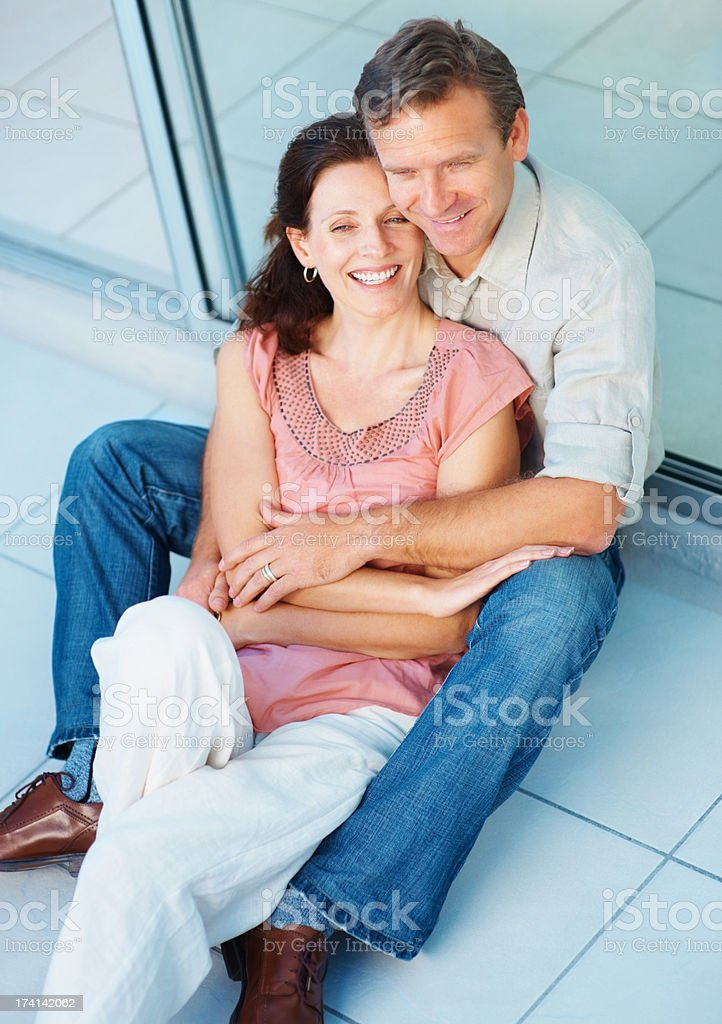 Smiling mature couple relaxing together on the floor stock photo