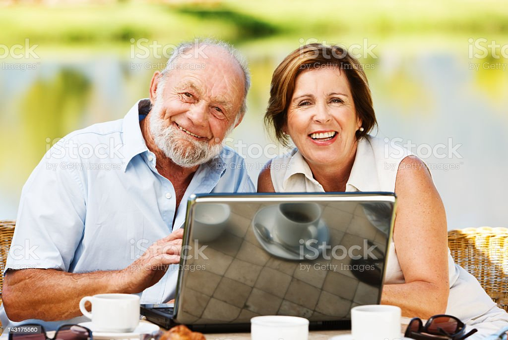 Smiling mature couple sharing laptop on lakeside terrace royalty-free stock photo