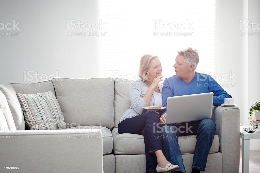 Smiling mature couple sitting at home in discussion with laptop stock photo