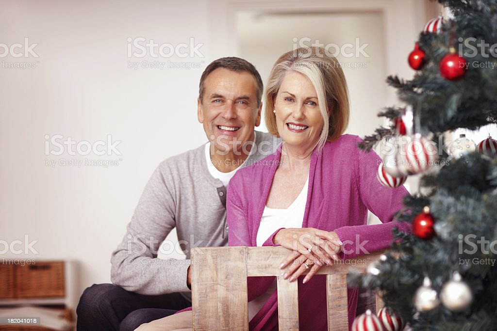Smiling mature couple sitting near a Christmas tree at home royalty-free stock photo