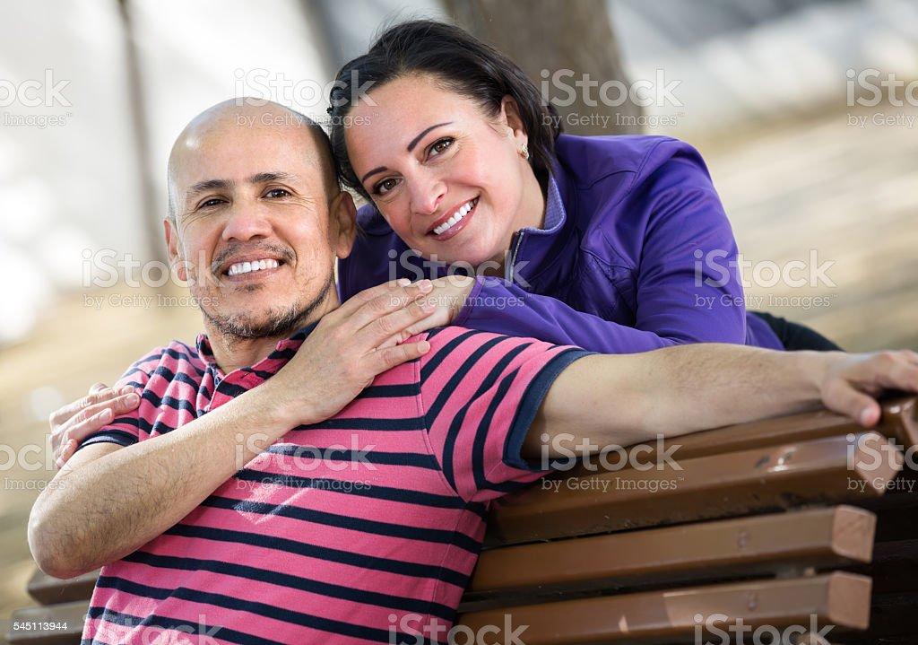 smiling mature couple sitting on the bench stock photo