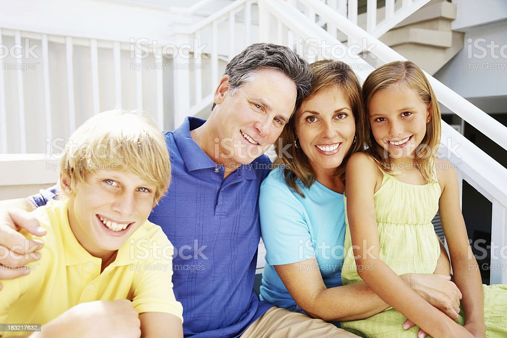 Smiling mature couple sitting with their children on staircase royalty-free stock photo