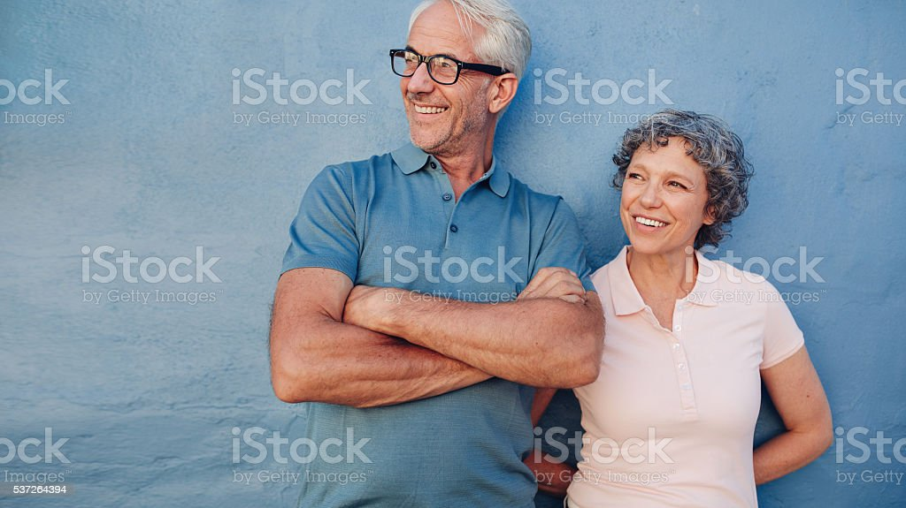 Smiling mature couple standing together and looking away stock photo