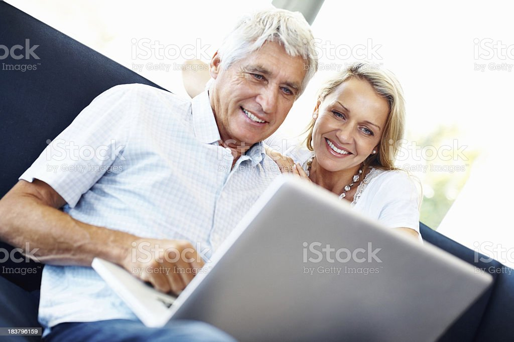 Smiling, mature couple using a laptop at home royalty-free stock photo