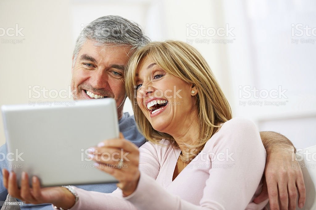Smiling mature couple using digital tablet royalty-free stock photo