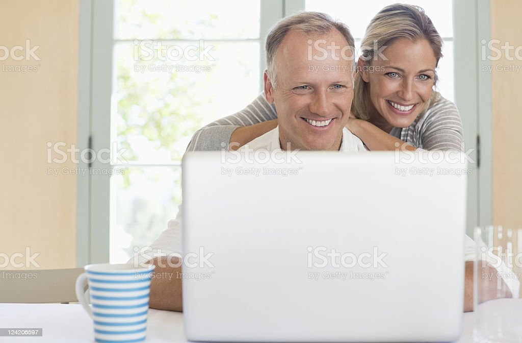 Smiling mature couple using laptop in the house royalty-free stock photo