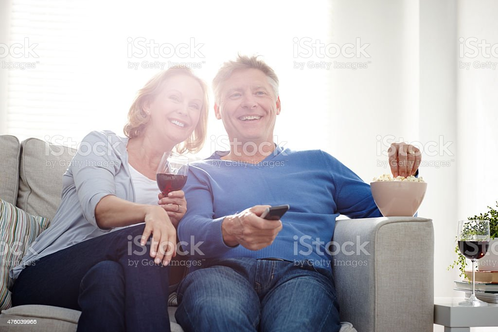 Smiling mature couple watching TV together stock photo