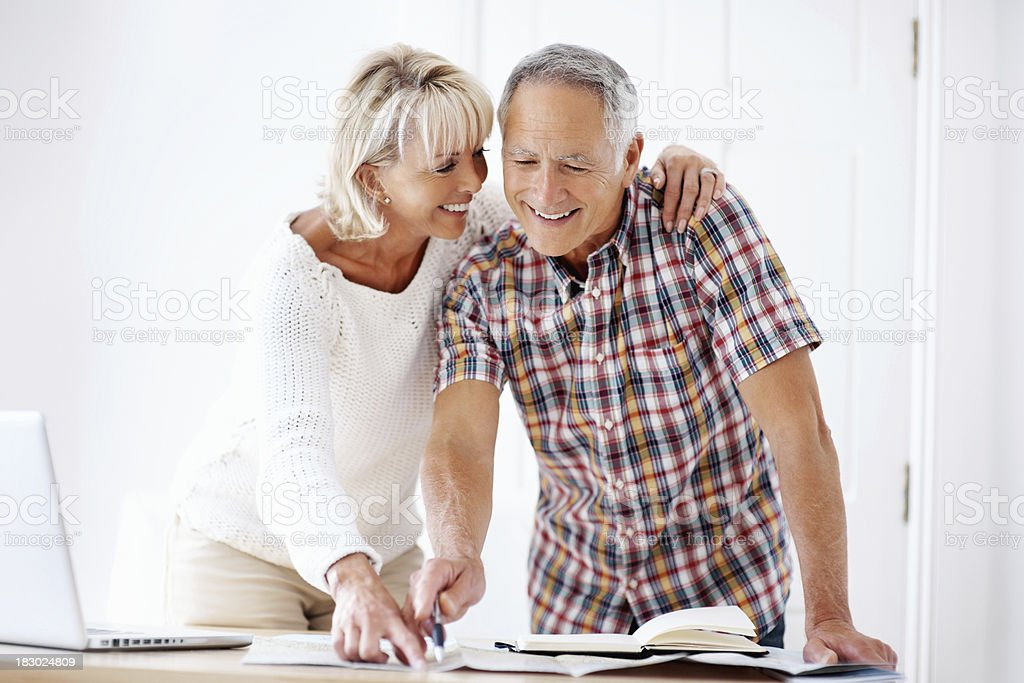 Smiling mature couple with book, map and laptop royalty-free stock photo