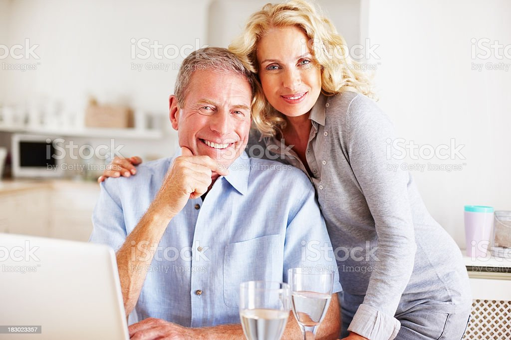 Smiling mature couple with wineglasses and laptop in kitchen royalty-free stock photo
