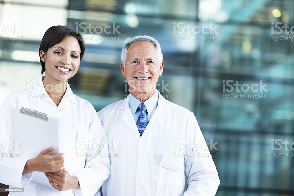 Smiling mature doctor with colleague stock photo