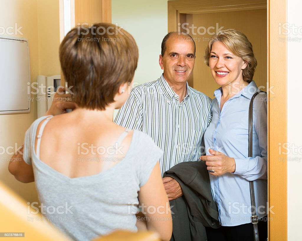 Smiling mature family couple visiting daughter stock photo