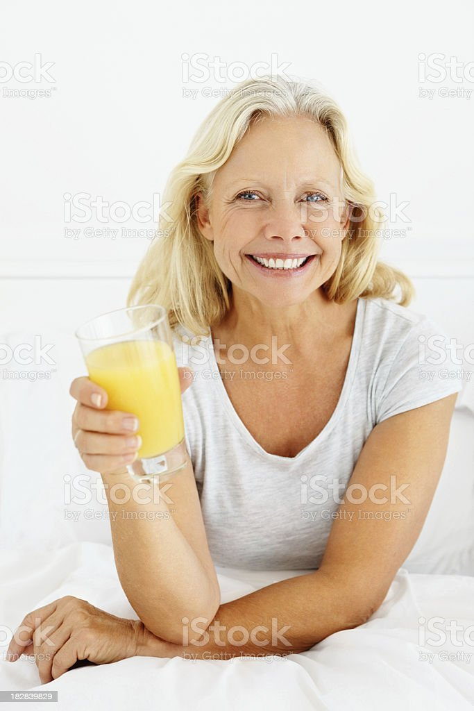 Smiling mature female holding a glass of juice royalty-free stock photo