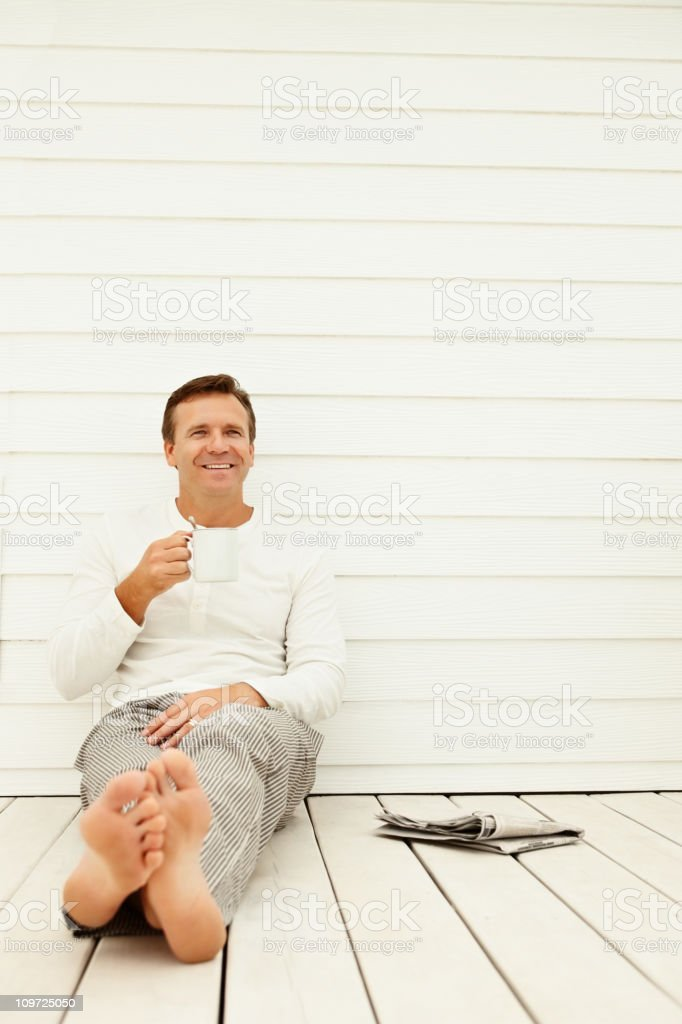 Smiling mature guy holding a coffee cup royalty-free stock photo