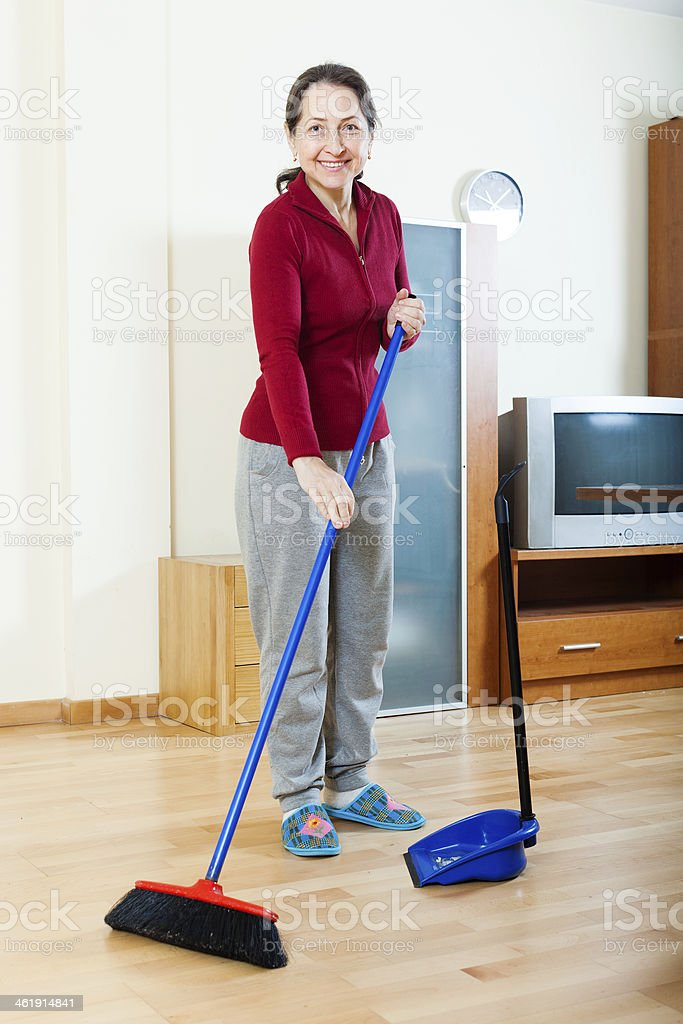 Smiling mature housewife cleaning  in living room stock photo
