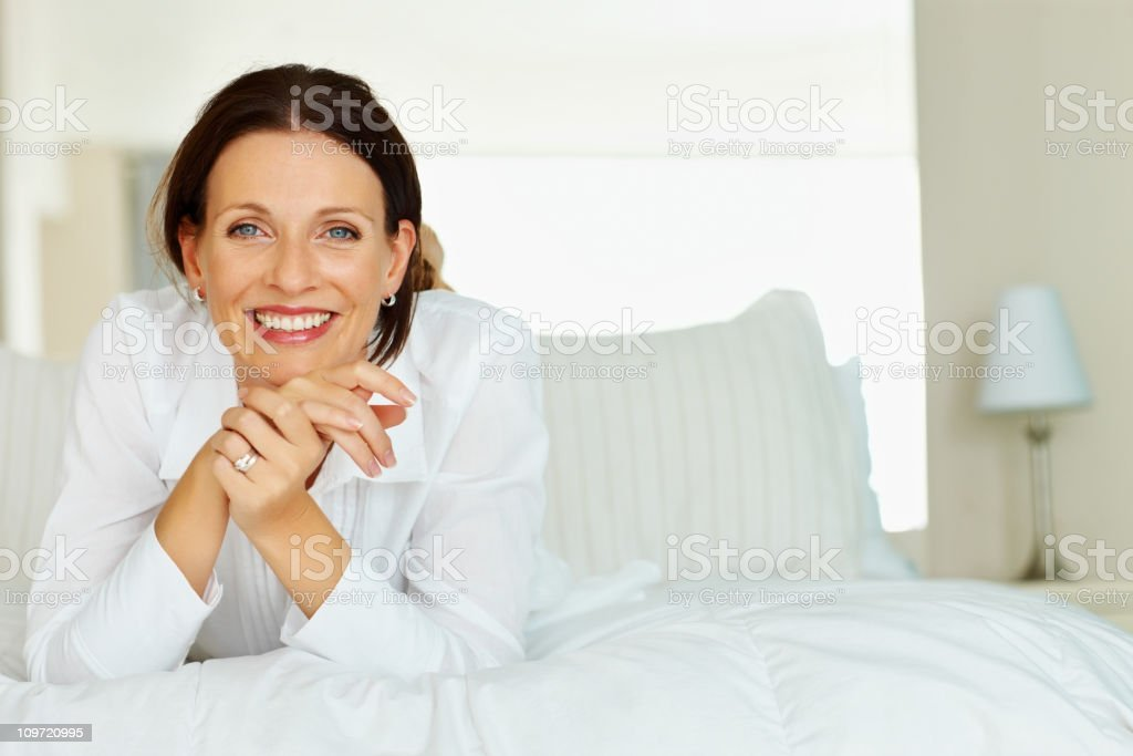 Smiling mature lady leans chin on her hands whilst on bed royalty-free stock photo