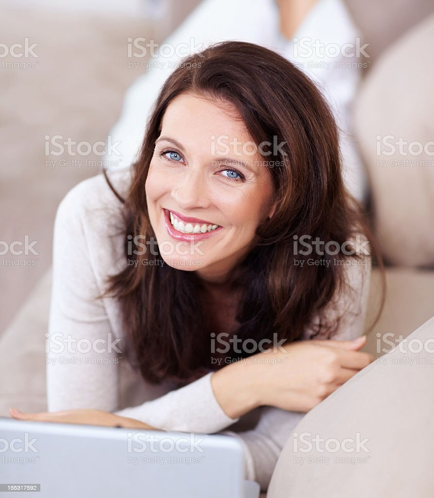 Smiling mature lady lying on couch and using laptop royalty-free stock photo