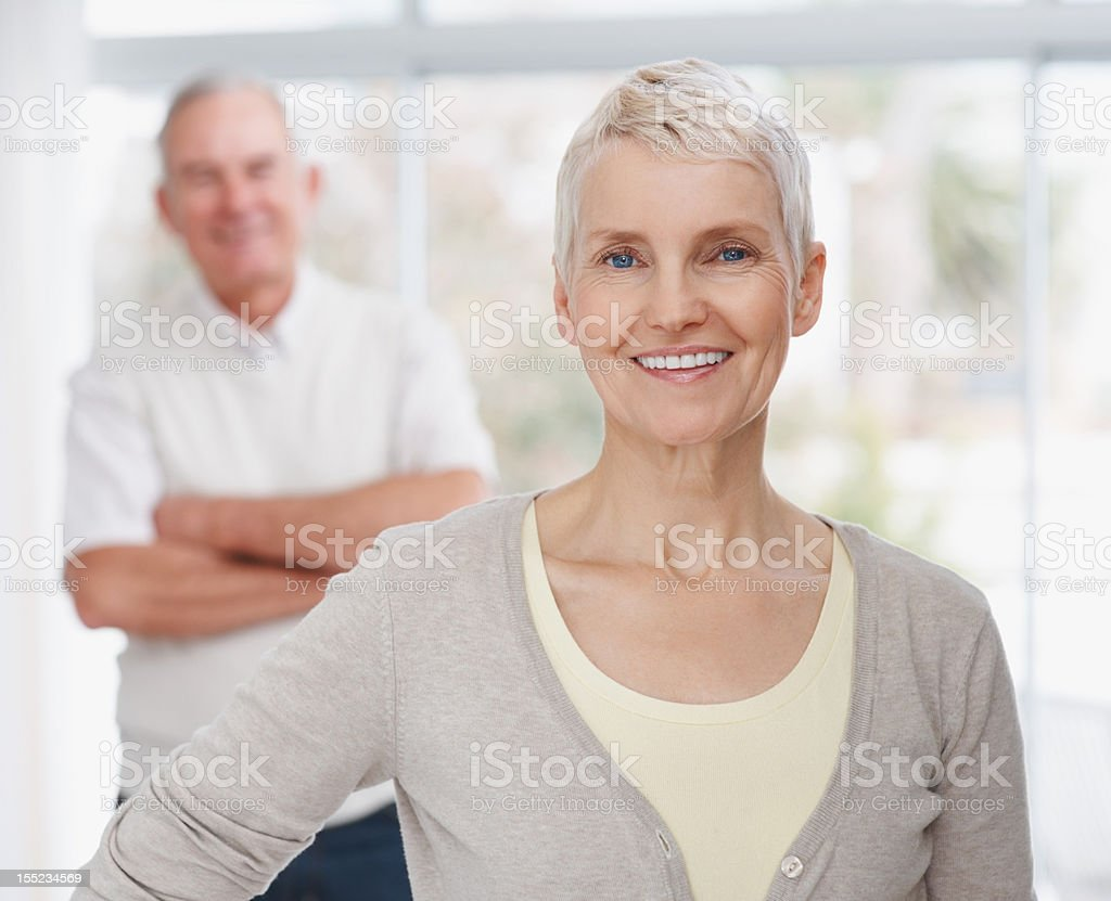 Smiling mature lady with husband in the background royalty-free stock photo