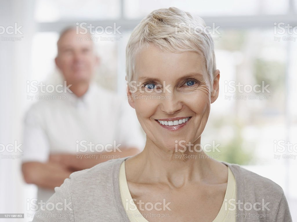 Smiling mature lady with man in the background royalty-free stock photo
