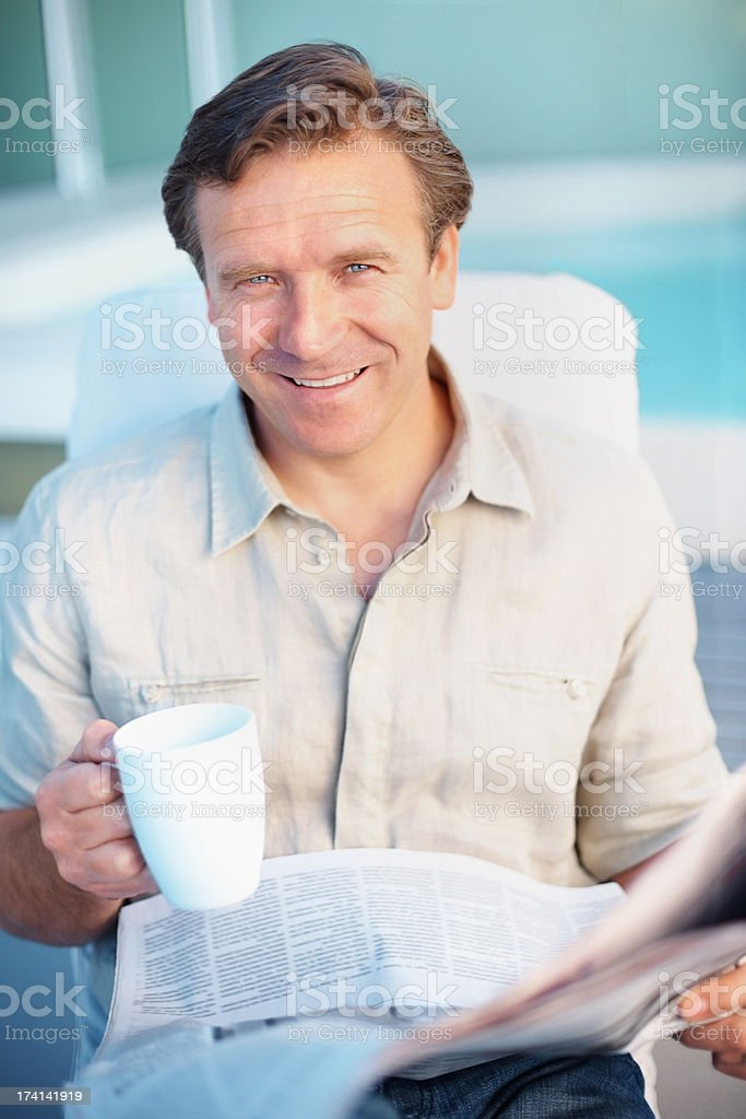 Smiling mature man drinking coffee while reading a newspaper stock photo