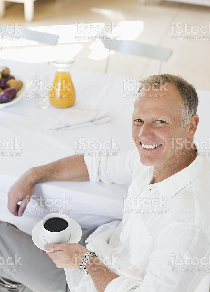 Smiling mature man having a cup of coffee at the breakfast table royalty-free stock photo