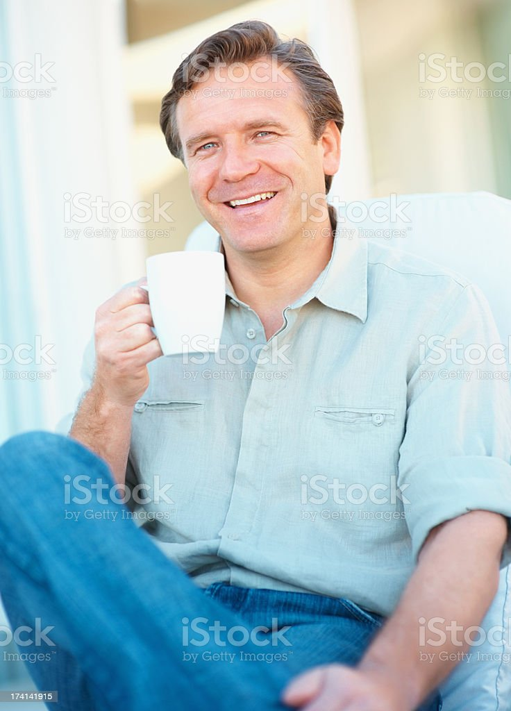 Smiling mature man holding a cup of coffee in hand stock photo